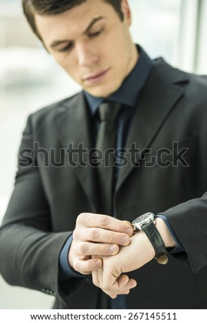 Handsome young businessman standing in modern office. - stock photo
