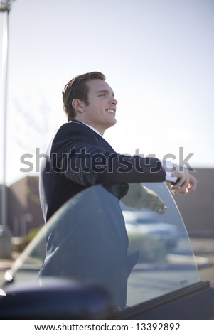 handsome young businessman standing outside of car with door open - stock photo