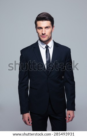 Handsome young businessman standing over gray background and looking at camera  - stock photo