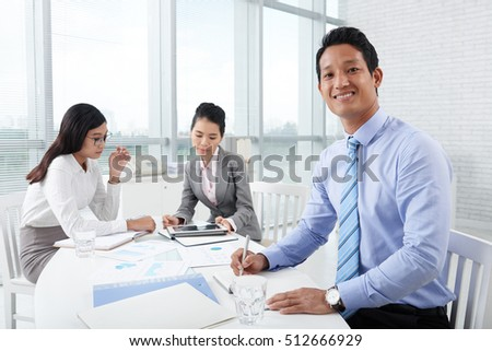 Handsome young businessman taking notes during meeting
