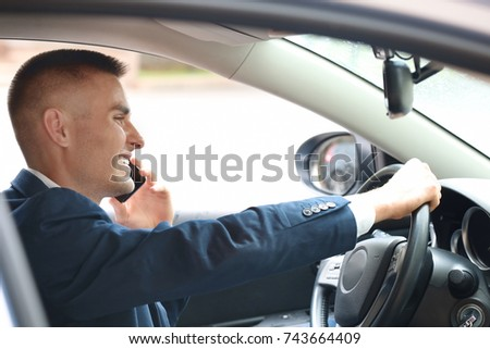 Handsome young businessman talking on mobile phone in modern car
