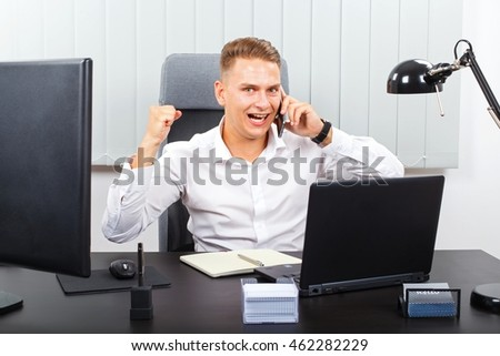 Handsome young businessman talking on the phone at office
