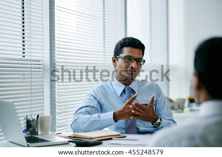 Handsome young businessman talking to his colleague - stock photo