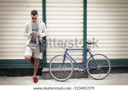 Handsome young businessman text messaging standing on the street with his bicycle beside him - stock photo
