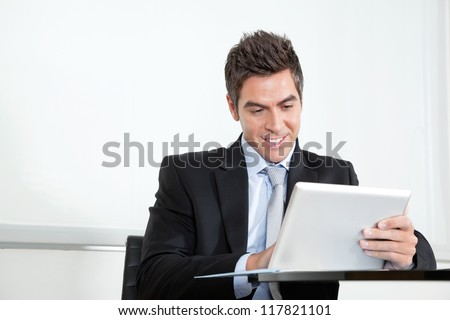 Handsome young businessman using digital tablet at desk in office - stock photo