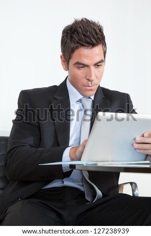 Handsome young businessman using digital tablet at desk in office