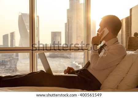 Handsome young businessman wearing formal white shirt and tie sitting on the bed with laptop in modern room. Self-employed person using smartphone in penthouse and looking at sunny city view in window - stock photo