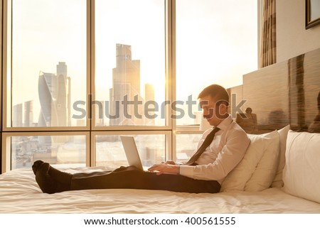 Handsome young businessman wearing formal white shirt and tie sitting on the bed with laptop in modern room with sunny city view in the background window. Full length. Lens flare - stock photo