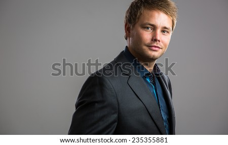 Handsome, young businessman - well dressed, against grey background - stock photo