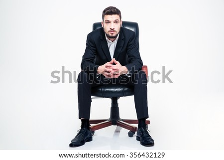 Handsome young businessman with beard in black suit and white shirt sitting in black office chair over white background - stock photo