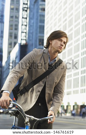 Handsome young businessman with bicycle on urban street - stock photo
