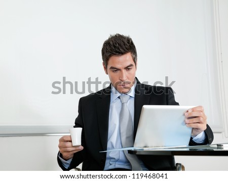 Handsome young businessman with coffee cup using digital tablet at desk in office - stock photo