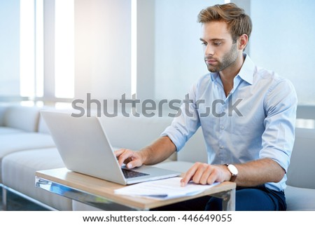 Handsome young businessman with designer stubble, sitting in a modern business lounge working on his laptop computer - stock photo