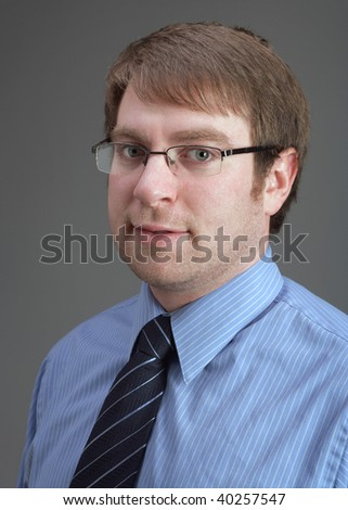 Handsome young businessman with glasses on grey background - stock photo