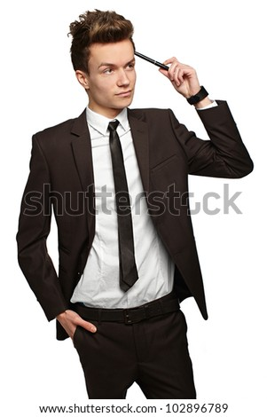 Handsome young businessman with pen in hand   with a slight smile on his face - stock photo
