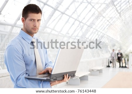 Handsome young businessman working on laptop at modern office lobby.? - stock photo