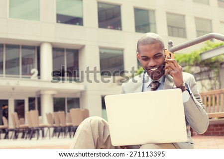 Handsome young businessman working with laptop outdoors talking on mobile phone. Instagram filter effect  - stock photo