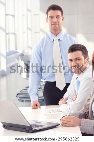 Handsome young businessmen working with laptop computer, looking at camera. - stock photo