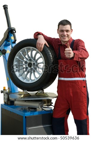 Handsome young car mechanic with wheel - stock photo