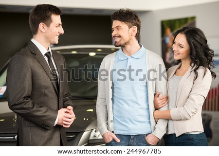 Handsome young car salesman is standing at the dealership telling about the features of the car to the customers. - stock photo