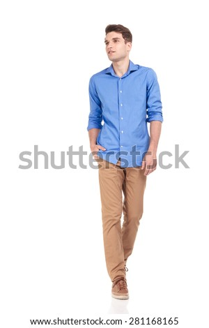Handsome young casual man walking with his hand in pocket on isolated background, looking away from the camera. - stock photo