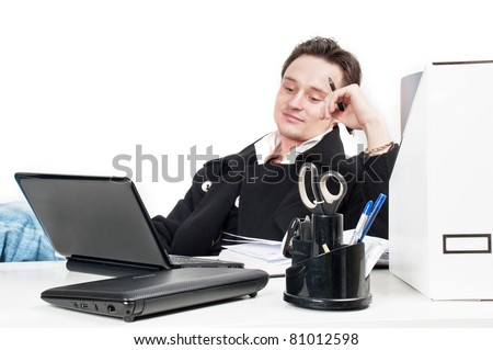 handsome young caucasian businessman with a pair laptops sitting at a table and work-flow in the office,guy at work in the office of the director,the manager works at the compute,isolated over white