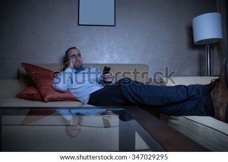 Handsome young caucasian man in a blue shirt and bow tie watching TV and calling by phone - stock photo