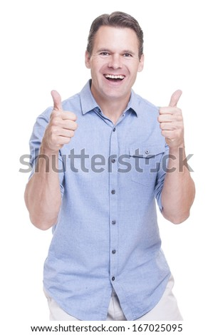 Handsome young Caucasian man in blue shirt smiles big and gives double thumbs up on white background