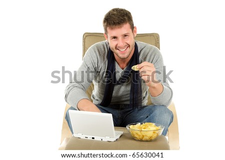 Handsome young caucasian man on sofa with netbook eating potatoes chips and surfing on internet. Studio shot. White background. - stock photo