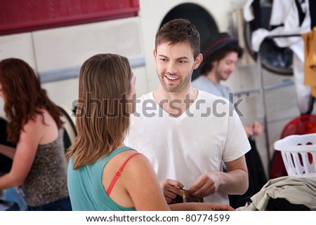 Handsome young Caucasian man talks with woman in laundromat - stock photo