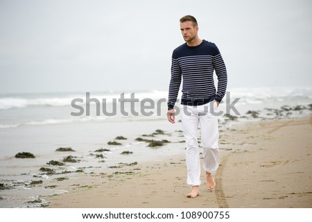 Handsome young Caucasian man walking alone with bare feet on the beach - stock photo