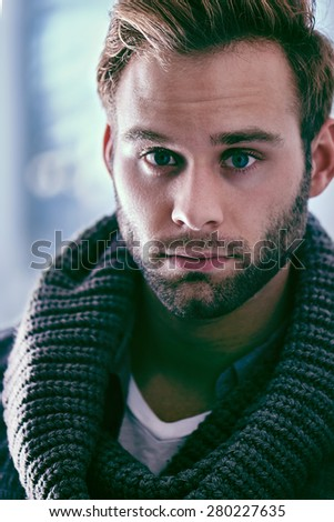 Handsome young caucasian man with dark hair and a trimmed beard looking at the camera, while wearing a scarf and white vest - stock photo
