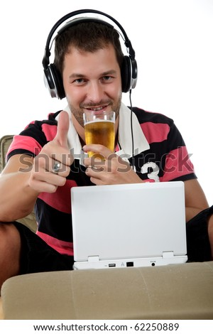 Handsome young caucasian man with headphones  and laptop on sofa listening  music from the internet and drinking beer. Thumb up. Studio shot. White background. - stock photo