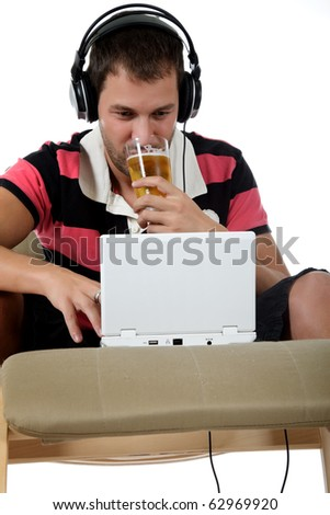 Handsome young caucasian man with headphones  and laptop on sofa listening  music from the internet and drinking beer. Studio shot. White background. - stock photo