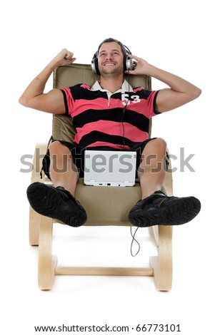 Handsome young caucasian man with headphones  and laptop, relaxing on sofa and listening to music from the internet. Studio shot. White background. - stock photo