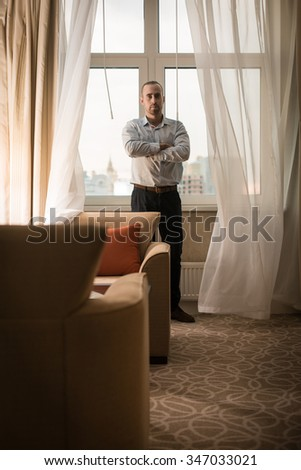Handsome young caucasian standing near the window - stock photo
