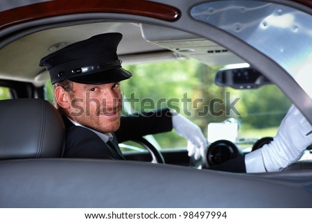Handsome young chauffeur in limousine, smiling.