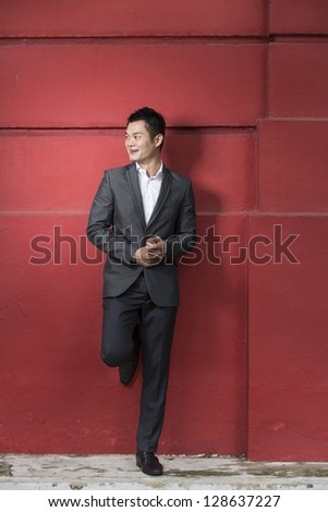 Handsome young Chinese business man leaning against a red wall. Happy Asian business man smiling and looking away.