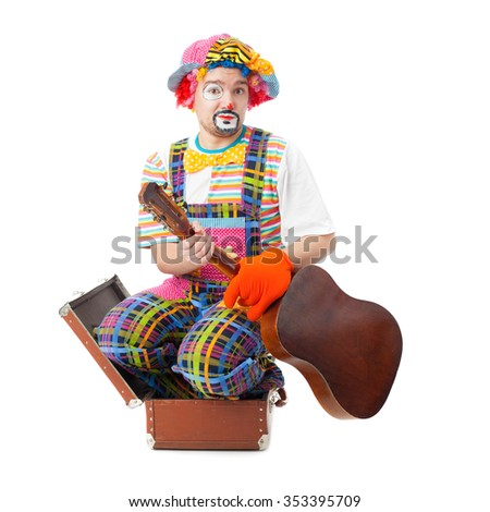 handsome young clown with the guitar and trunk - stock photo