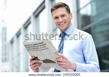 Handsome young corporate male holding newspaper