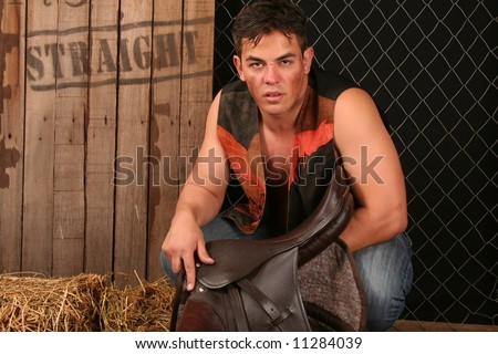Handsome young cowboy next to saddle sitting on hay - stock photo