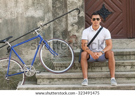 Handsome young cyclists resting on the steps of the building in the old town with his bicycle beside him - stock photo