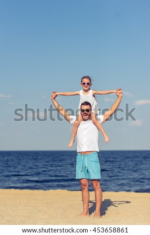 Handsome young dad and his cute little daughter are looking at camera and smiling, standing on the beach. Girl is sitting on her father's shoulders - stock photo