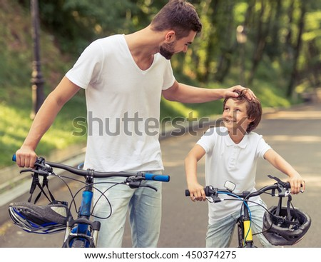 Handsome young dad and his cute little son are looking at each other and smiling while riding bikes in park. Father is patting his son - stock photo