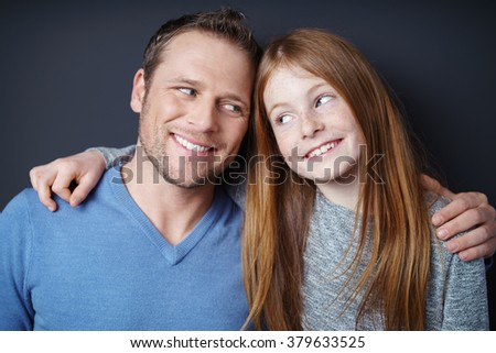 Handsome young Dad and his pretty redhead daughter giving each other teasing knowing looks, head and shoulders on dark background - stock photo
