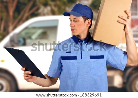 Handsome young delivery man carrying carton box. - stock photo