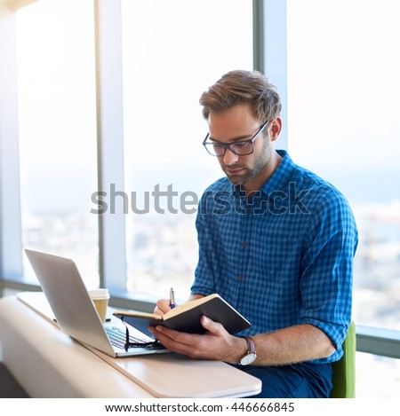Handsome young designer with modern spectacles, sitting in a bright space with large windows, working with his laptop and diary, making future plans - stock photo