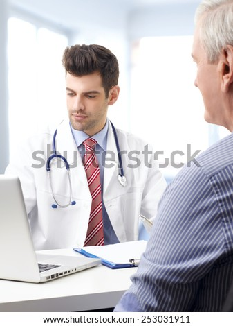 Handsome young doctor consulting with elderly patient while sitting at desk in front of computer.  - stock photo