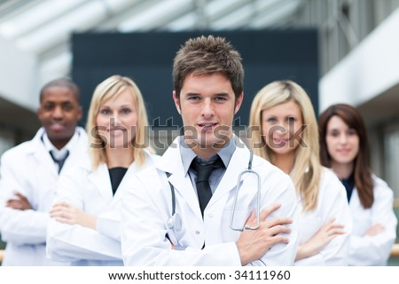 Handsome young doctor leading his team with folded arms - stock photo