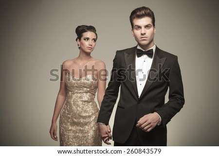Handsome young elegant man holding his girlfriend by hand while she is looking away from the camera. - stock photo